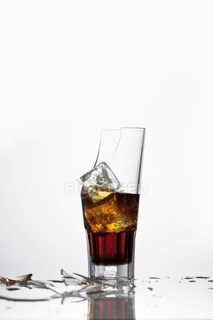 Closeup view of broken glass with Cola and ice cubes — Stock Photo
