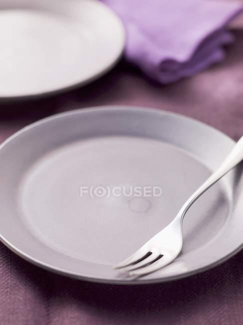 Plato vacío con tenedor - foto de stock