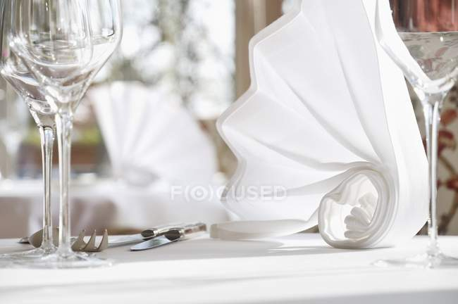 Closeup view of folded white napkins on a laid table — Stock Photo