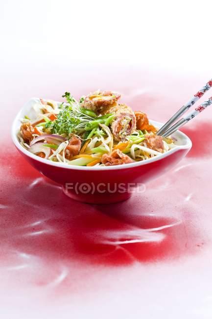 Verduras fritas con jamón y berro en tazón rojo sobre superficie roja - foto de stock