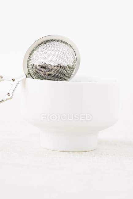 Tea strainer balanced on bowl — Stock Photo