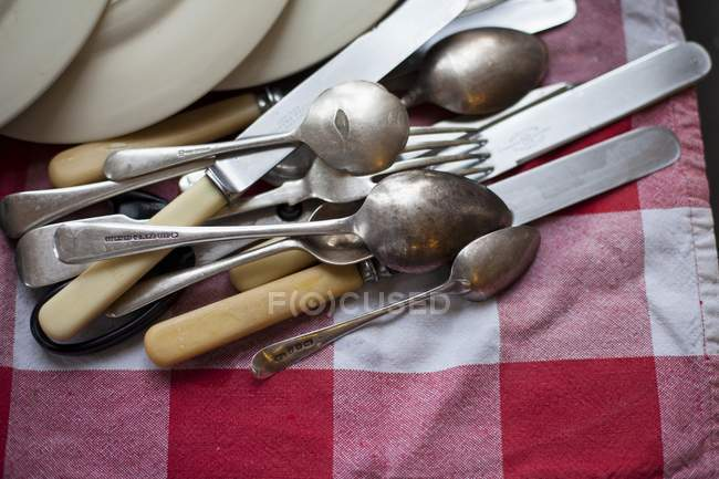 Closeup view of cutlery and plates lying on a towel — Stock Photo
