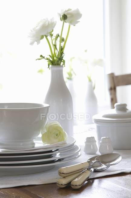 Stacked crockery and cutlery on a table with a vase of white ranunculus flowers — Stock Photo