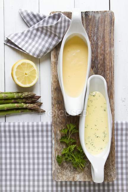 Two sauces served with asparagus on wooden desk — Stock Photo