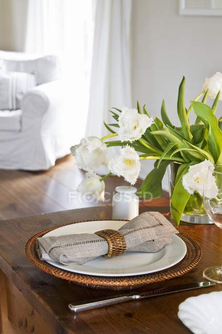 Still life with a bunch of white tulips in a glass vase and a place setting with a basket plate — Stock Photo
