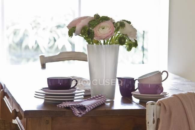 Дерев'яний стіл з накопиченням посуд і декоративні купу ranunculus квіти і листя — стокове фото