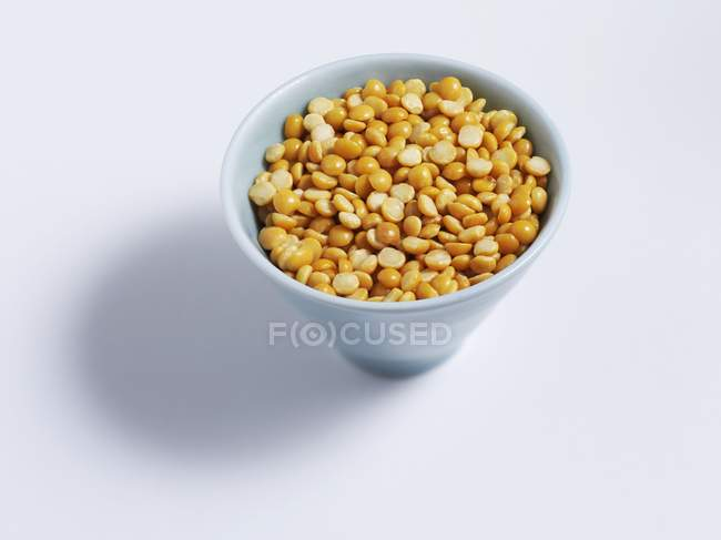 Elevated view of yellow dry pea halves in a bowl — Stock Photo