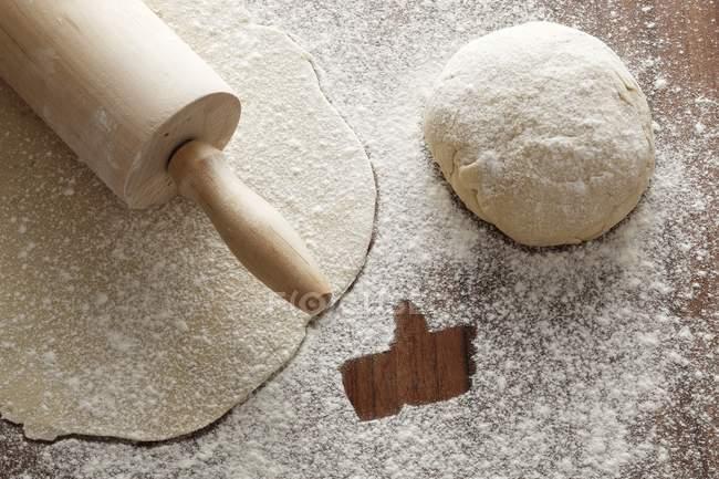 Closeup vista saída rolou massa com um rolo, uma bola de massa e farinha com um símbolo como — Fotografia de Stock