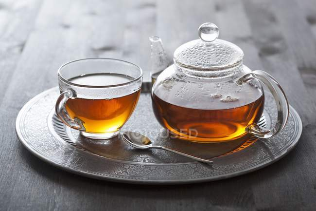 Tea in glass cup and teapot — Stock Photo
