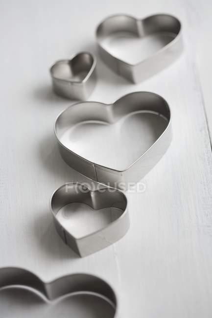 Крупный план кусачек для печенья в форме сердца на белой поверхности — стоковое фото
