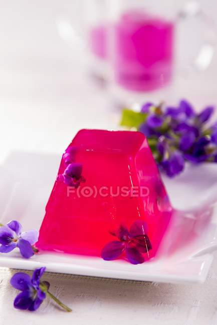 Violet jelly decorated with flowers — Stock Photo