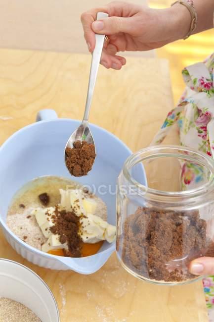 Mulher, adicionando os ingredientes da massa de biscoito na tigela — Fotografia de Stock