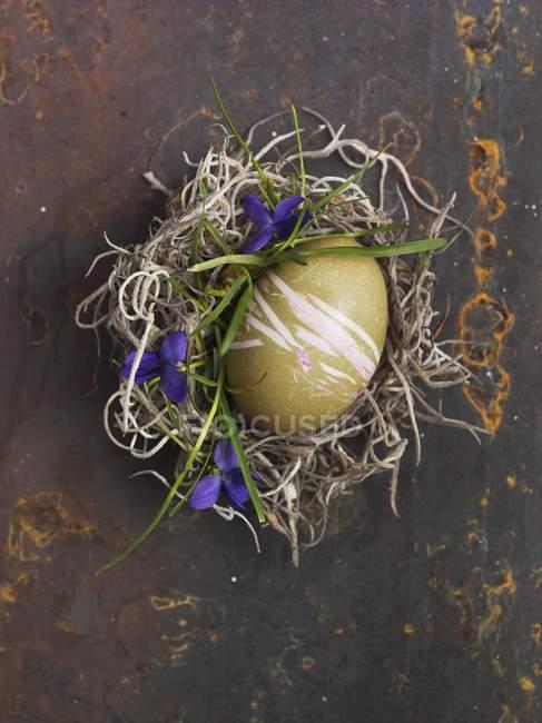 Vista superior de un verde decorado huevos de Pascua en un nido - foto de stock