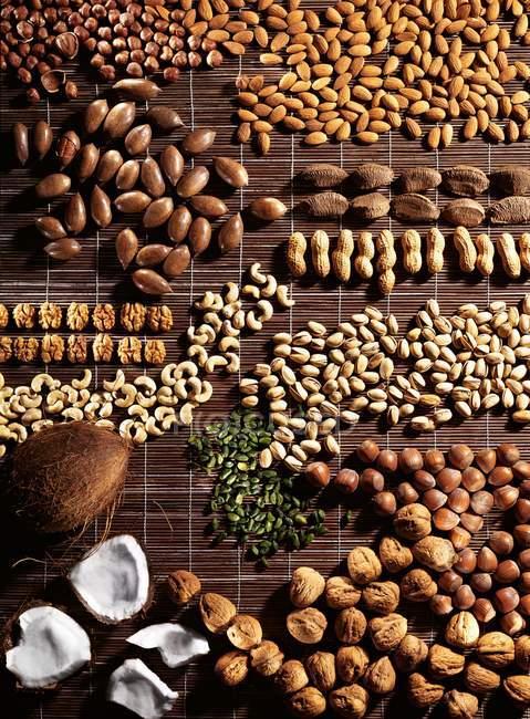 Vista superior de frutos secos variados dispuestos sobre una estera de rafia marrón - foto de stock