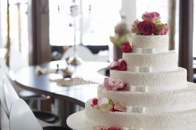 Свадебный торт украшен белыми лентами — стоковое фото