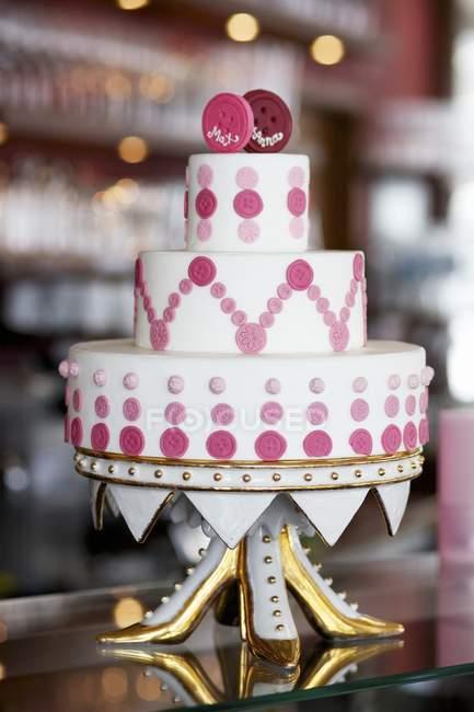 Свадебный торт, украшенный розовыми кнопок — стоковое фото