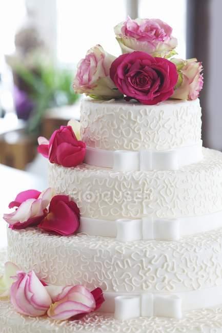 Свадебный торт, украшенный свежие розы — стоковое фото