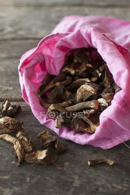 Vista de primer plano de setas secas en una bolsa de tela rosa - foto de stock