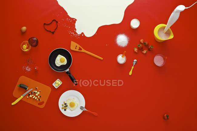 Assorted breakfast ingredients over red surface — Stock Photo