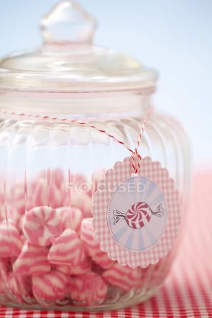 Nahaufnahme von rosa und weiß gestreiften Bonbons im Glas mit Anhänger — Stockfoto