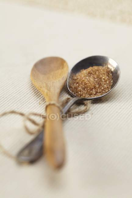 Wooden and Silver Spoons with brown sugar — Stock Photo