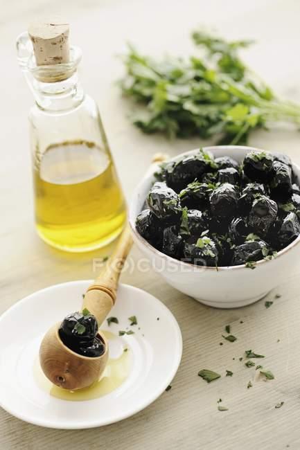 Olives noires aux herbes dans un bol — Photo de stock