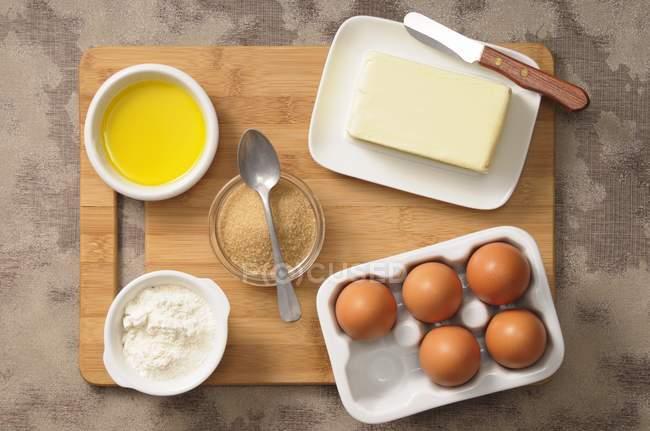 Vista superior de una variedad de ingredientes para hornear incluyendo huevos, azúcar, mantequilla, harina y aceite - foto de stock