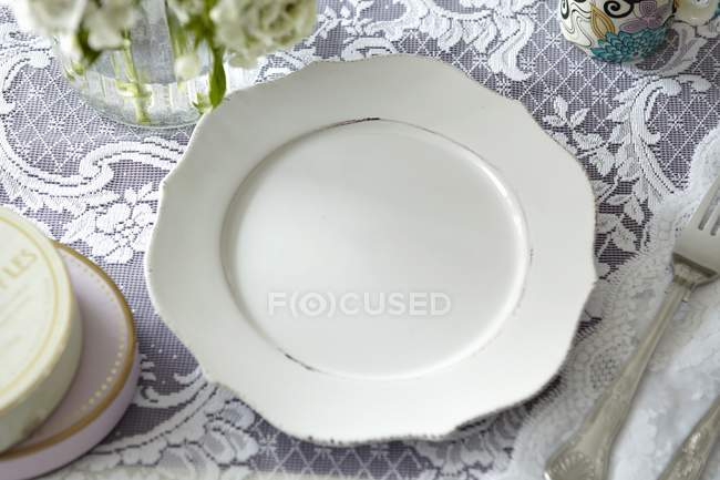 Closeup view of a white plate on a lace cloth — Stock Photo
