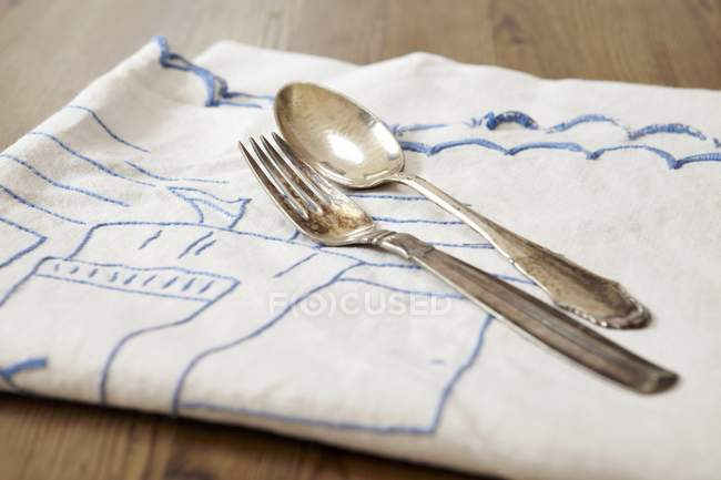 Closeup view of a silver fork and a spoon on a towel — Stock Photo