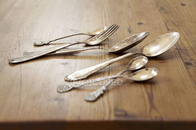 Closeup view of silver cutlery on a wooden table — Stock Photo