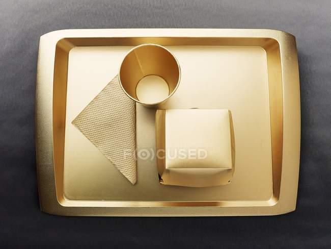Vue du dessus de plateau jetable de couleur or, tasse, serviette et boîte en carton — Photo de stock