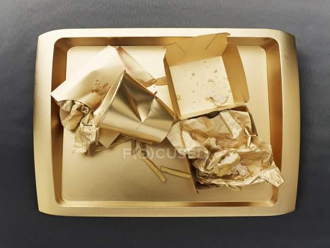 Vue de dessus des restes d'un repas de restauration rapide sur un plateau couleur or — Photo de stock