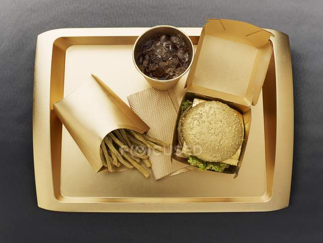 Top view of fast food with a gold colored disposable food set — Stock Photo