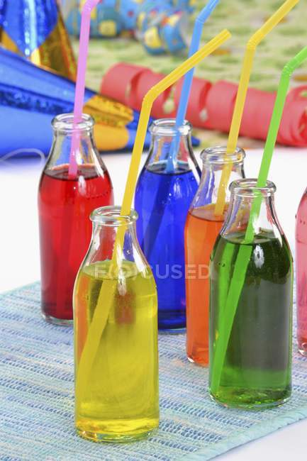 Closeup view of colorful drinks in bottles with drinking straws — Stock Photo