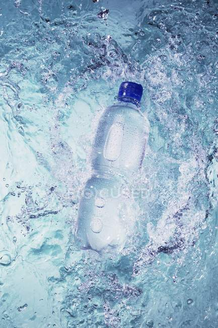 Elevated view of plastic bottle falling into water — Stock Photo