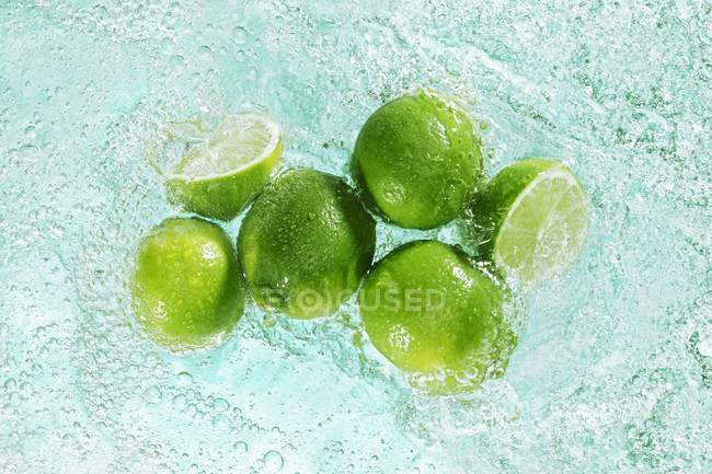 Limes in sparkling water — Stock Photo