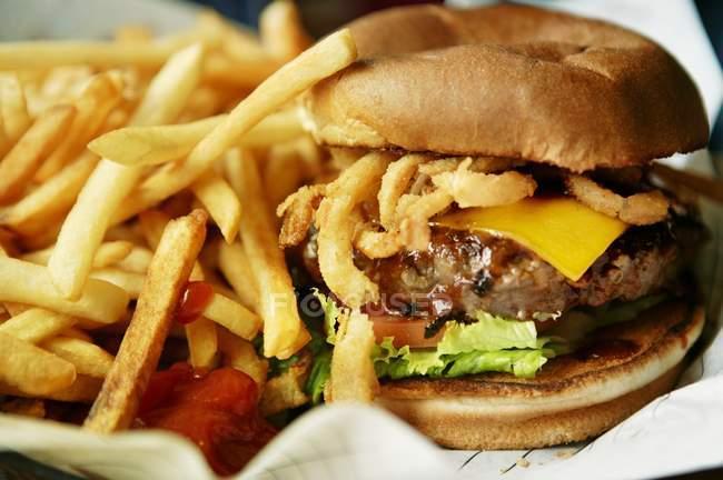 Hamburguesa de queso con papas fritas - foto de stock