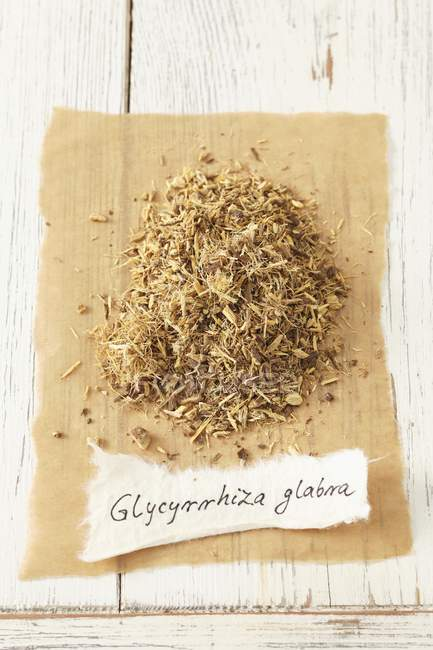 Closeup view of dried liquorice root heap with tag — Stock Photo