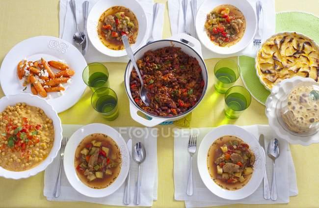 Асорті апетитних страв у каструлі і на тарілки над жовтий поверхні — стокове фото
