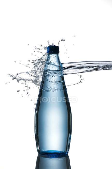 Closeup view of splash hitting a bottle of water — Stock Photo
