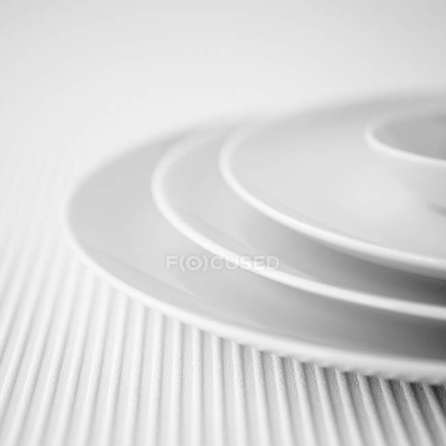 Vista de primer plano de apilados tres platos blancos y tazón - foto de stock