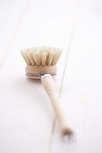 Primo piano vista di una spazzola di lavaggio di legno su assi di legno — Foto stock