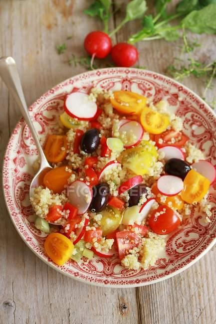 Insalata di quinoa con ravanelli e pomodori di ciliegia sulla zolla con il cucchiaio di legno sulla superficie di legno — Foto stock