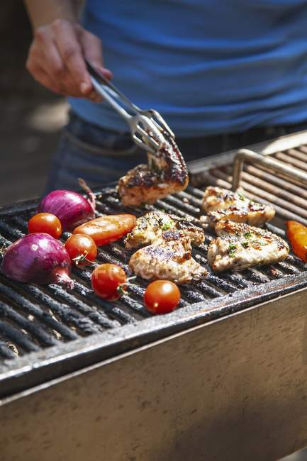 Chicken wings and vegetables on the barbecue — Stock Photo