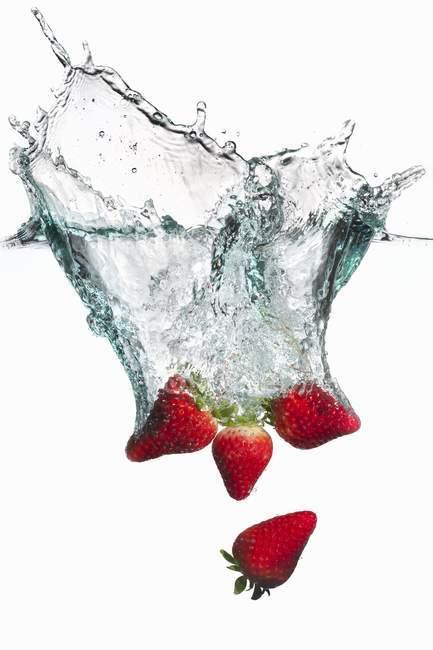 Fragole che cadono in acqua — Foto stock