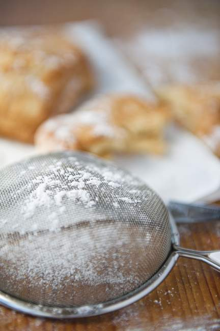 Closeup view of sieve with icing sugar and baked pastries on the background — Stock Photo