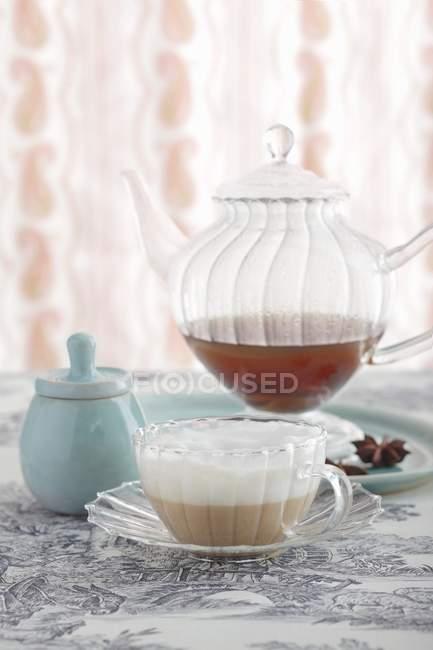 Chai latte en verre teacup devant une théière en verre — Photo de stock