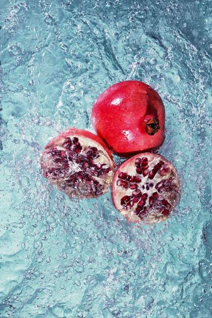 Pomegranate with halves in water — Stock Photo