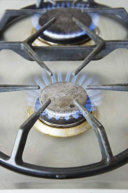 Closeup view of lit gas rings on the hob — Stock Photo