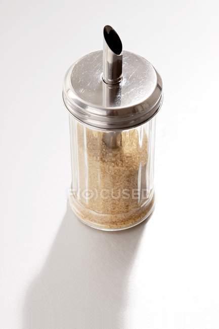 Closeup vista do açúcar shaker cheio de açúcar mascavo no fundo branco — Fotografia de Stock